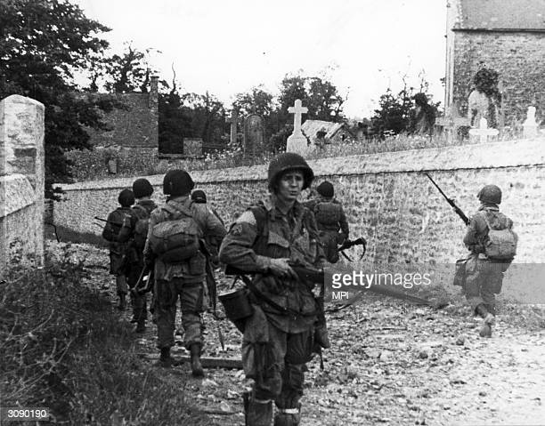 American paratroopers having made successful landings at Utah Beach advance cautiously through a French cemetery at St Marcouf