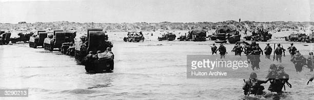American troops part of the Allied Expeditionary Force wading ashore beside their amphibious tanks during the initial landings in France