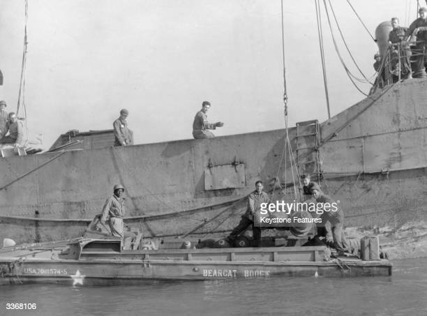 Bombs are unloaded from a Norwegian merchant ship onto an American amphibious landing craft during the Invasion of Normandy by allied forces