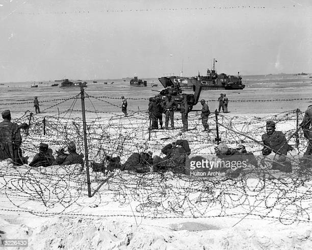 German prisoners of war are detained behind barbed wire by American soldiers on Utah Beach on the coast of France World War II
