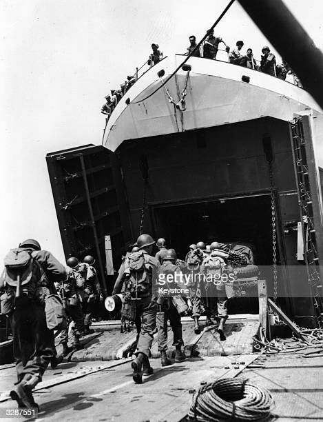 Members of a US combat engineer unit marching aboard an LST or Landing ShipTank at an English port ready for the invasion of Europe