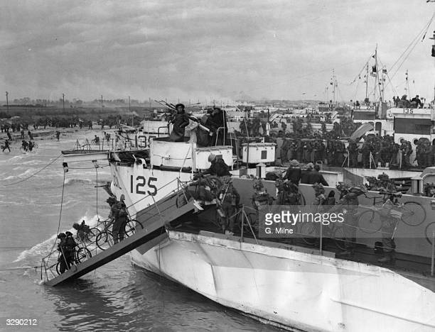 Troops of the Canadian 3rd Division leaving their ship with their bicycles at Juno beach along the coast of Normandy France on DDay