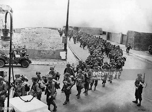 US Army troops seen marching through the streets of an embarkation port on the coast of England on their way over to Normandy France