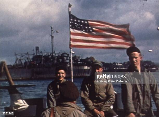 Troops travel the English Channel on a barge en route to Normandy, France for the D-Day Invasion, World War II. An American flag flies behind them.