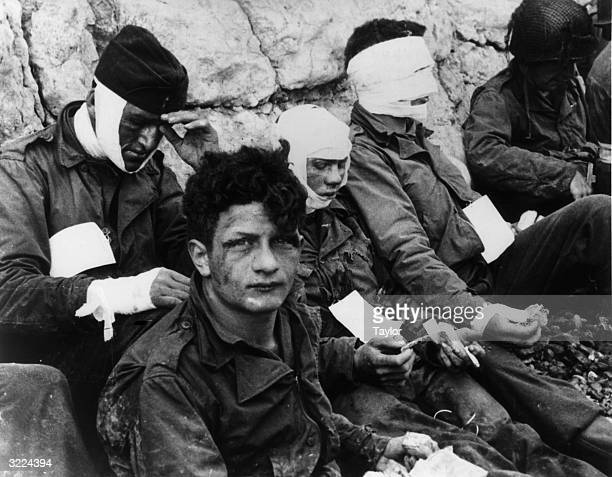 Wounded US soldiers of the 3rd Battery 16th Infantry Regiment 1st US Infantry Division lean against chalk cliffs while eating and smoking after...