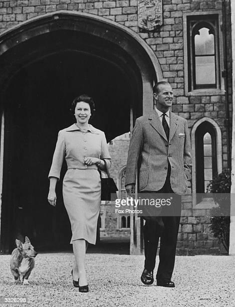 Queen Elizabeth II and Prince Philip the Duke of Edinburgh with the Queen's corgi Sugar walking near the George IV gateway at Windsor Castle