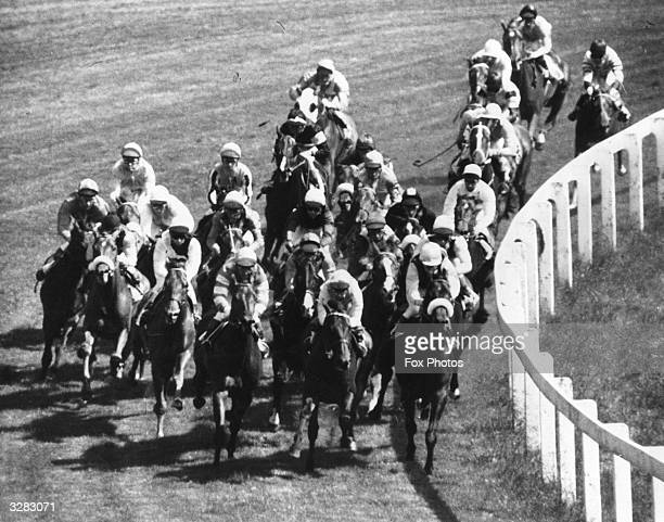 The field of horses in the Derby at Epsom round the 'Tattenham Corner' and battle towards the finish line. The race was won by Morston ridden by...