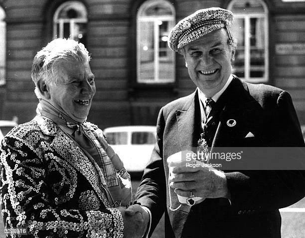 George Hitchen the Pearly King of the City of London England in his traditional suit covered with pearl buttons He is shaking hands with the Lord...