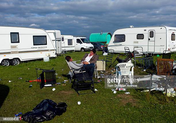 Two revellers asleep as the sun rises over their caravans at Appleby Horse Fair The travellers had partied long into the night to celebrate a family...