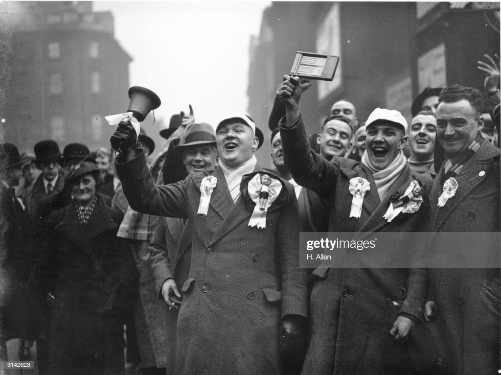Ringing handbells, waving rattles and wearing rosettes, Manchester City supporters arriving at Euston Station, London for the cup tie against Millwall.