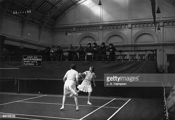 Group of spectators watching a match at the Royal Horticultural Hall in Westminster during the All England Badminton Championship.