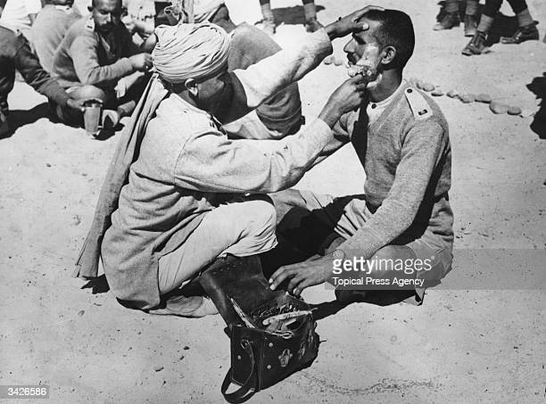 The military camp barber at work on one of the Allied Indian troops in the Egyptian desert