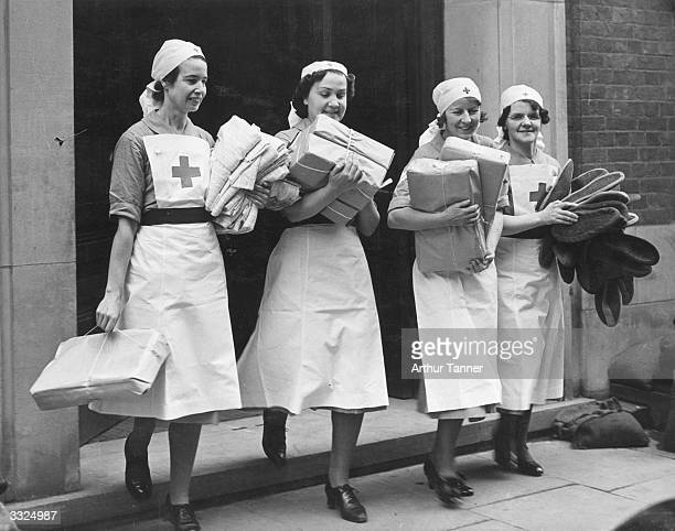 Four British Red Cross nurses carrying gift parcels from the USA and elsewhere which are to be distributed to patients in various hospitals