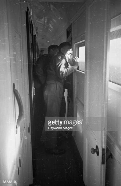 Wounded veterans of the battle of El Alamein crowd the corridors to look out of windows in a train bringing them back to England Original Publication...