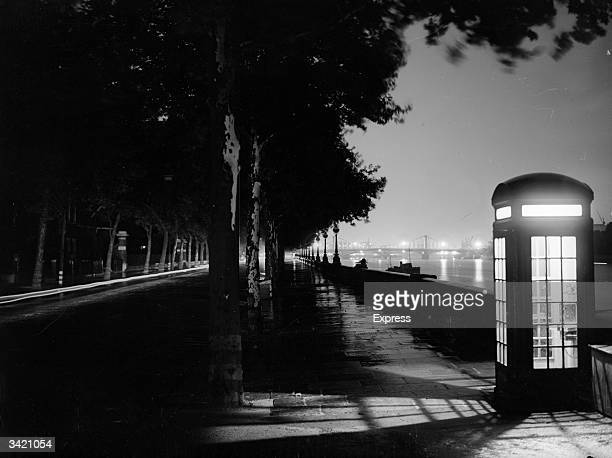An illuminated telephone box lights up the path alongside the Thames on the Embankment at night