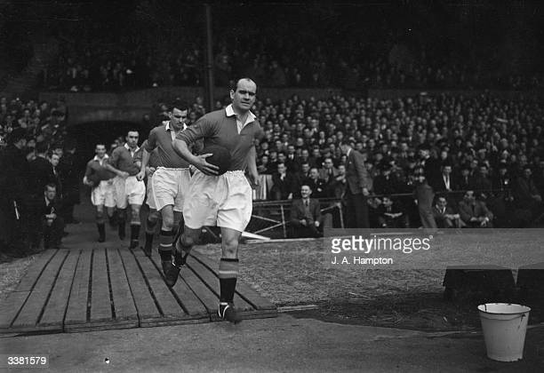 Johnny Carey the Manchester United captain leads his team out onto the pitch