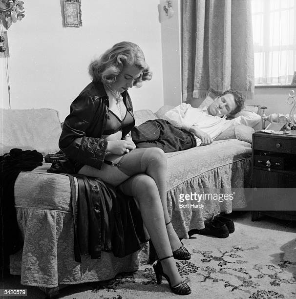 A wife's expectations are dashed as her husband falls asleep From a Picture Post photo story about the problems exprisoners have adjusting to home...
