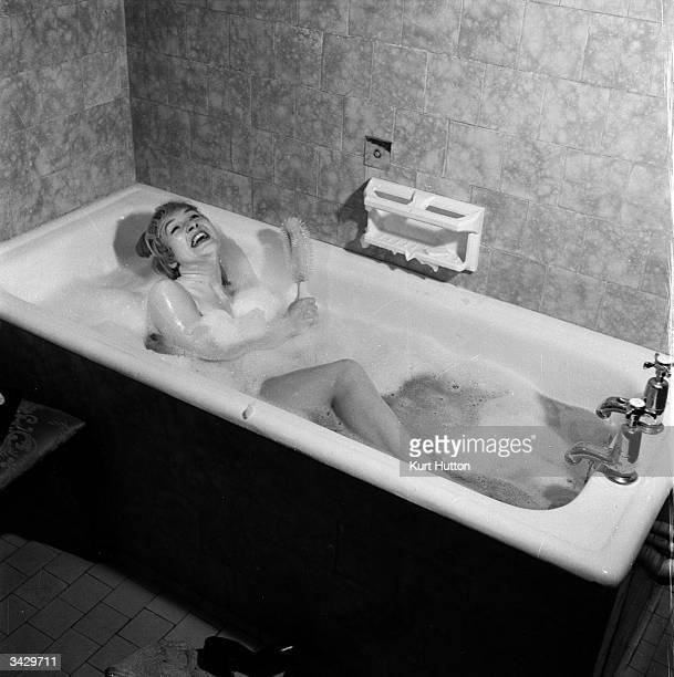 Film extra Barbara Morris stars in a Picture Post reconstruction of her dream film role here relaxing in a bubble bath in the style of a glamorous...
