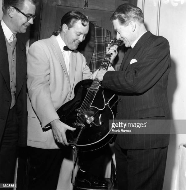 Famous American rock 'n' roller Bill Haley shows his electric guitar to Rt Reverend RW Stannard the Bishop of Woolwich March 1957