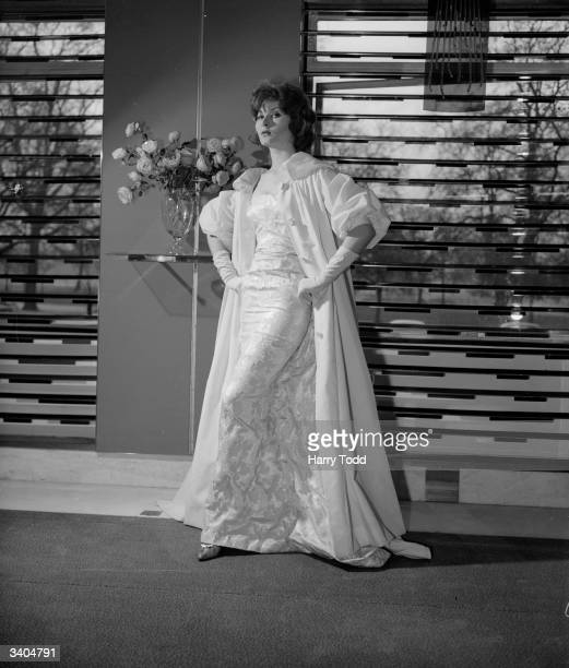 Model Liese Deniz modelling an evening dress by John Cavanagh Slim fitting in front with aflowing back panel of silver and gold nylon brocade The...