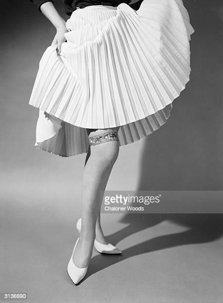 A sixties fashion model lifting her pleated hemline to reveal an ornate garter above the knee
