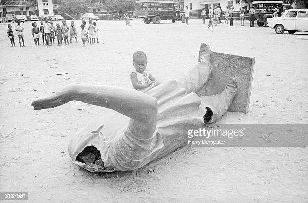 Child stands by a fallen statue of the self appointed president of Ghana, Kwame Nkrumah during the coup that overthrew his dictatorship.