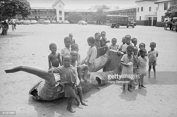 Children around a fallen statue of the self appointed president of Ghana Kwame Nkrumah during the coup that overthrew his dictatorship