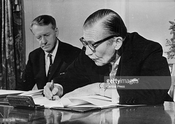The Rhodesian Premier Ian Smith looks on as Clifford Dupont signs the dissolution of Parliament in Salisbury Rhodesia This proclamation came on the...