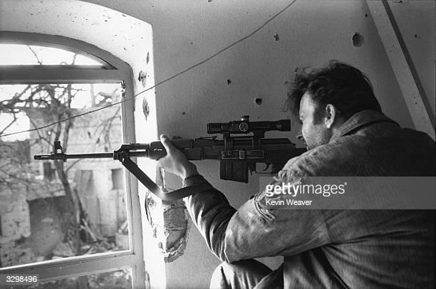 A Serbian sniper fires through a window in Brcko North Eastern Bosnia