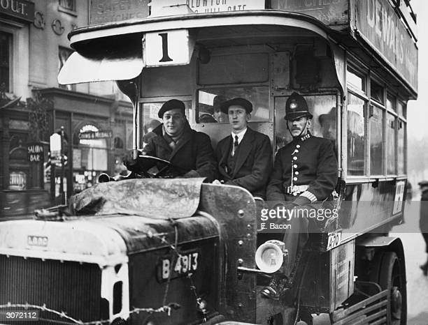 A policeman rides beside a volunteer bus driver during the General Strike There is barbed wire round the bonnet to stop strikers getting at the...