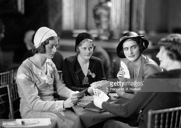 Miss Peggy Lubbock Miss Lois Hammond and Miss Barbara Cunard engrossed in a bridge tournament at Londonderry House in London