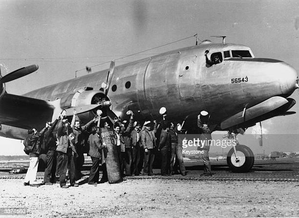 On the tarmac at RheinMain Frankfurt crew of a Transport Squadron Six plane belonging to the US navy involved in the Berlin Airlift raise a cheer on...