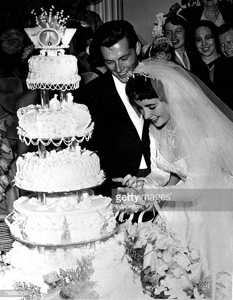 6th May 1950 Shown here are the newly wedded couple Conrad Hilton Jnr and his actress bride Elizabeth Taylor pictured cutting the cake at a huge...