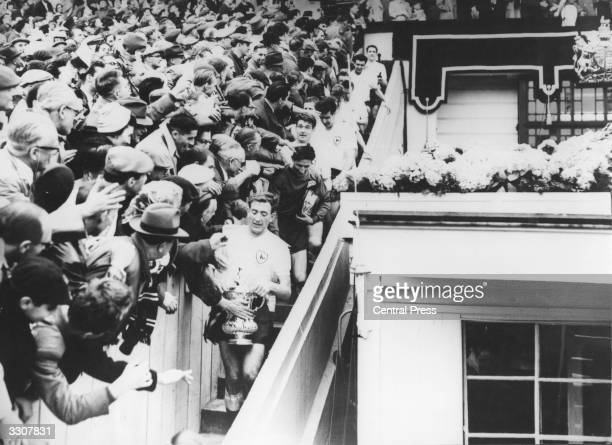Tottenham Hotspur captain Danny Blanchflower carries the FA Cup trophy as he leads his teammates down Wembley's famous steps after the Cup and medal...
