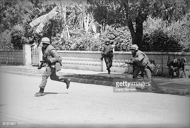 American soldiers running across a street while stationed in Dominica during the civil war which led to the island becoming an internally...