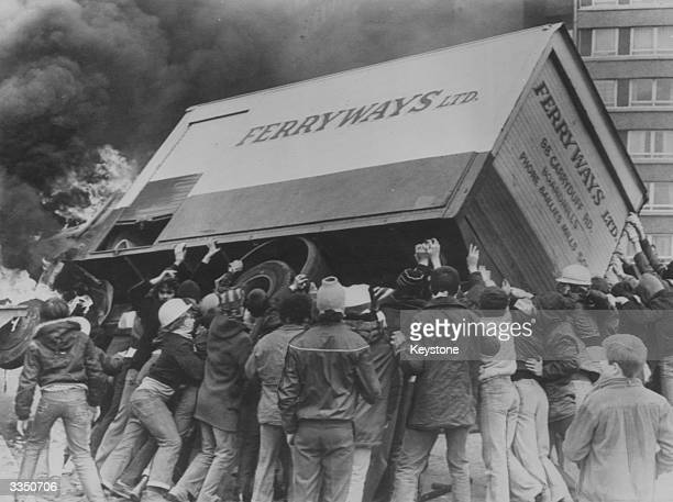Rioters turn a burning lorry into a barricade in the Divis Flats area of Belfast after violence erupted following the death of Irish Republican Army...