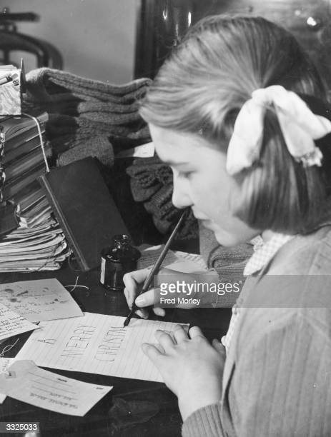 Pupil of the Laura Place Emergency School in Clapton, London, writes a Christmas card to the men on board 'The Empire Sailor'. The children have...