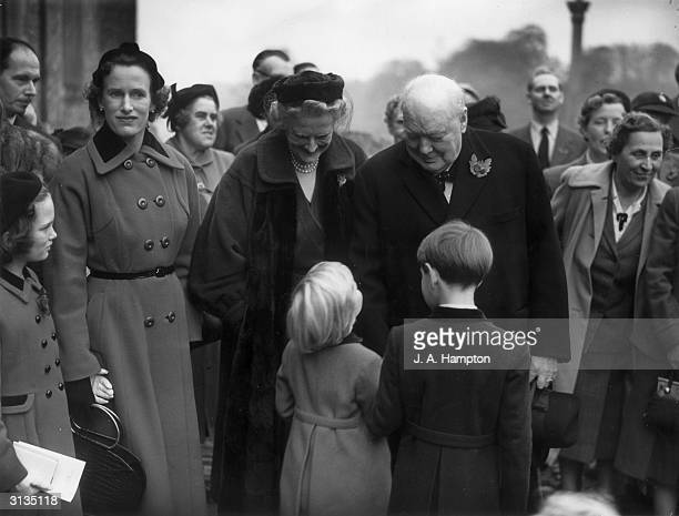 British Conservative politician Winston Churchill and his wife Clementine chatting to two of their grandchildren Emma and Nicholas Soames at the...