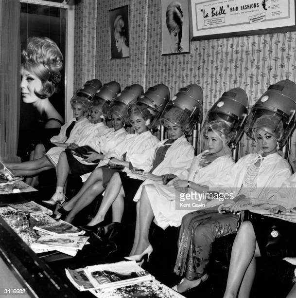 Group of Miss World contestants line up under the hairdryers at La Belle hairdressing salon in Aldwych, London. They include Miss Finland, Miss...