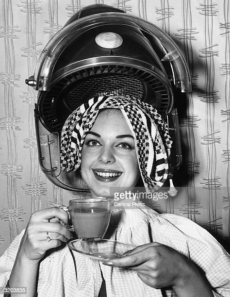 Louise Crous Miss South Africa 1963 drinks a cup of coffee as she gets her hair done in preparation for the Miss World beauty pageant London