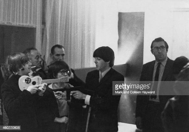 Paul McCartney points a replica machine gun at Ringo Starr while Ringo points a toy Beatle guitar at Paul backstage at the Gaumont Cinema in...