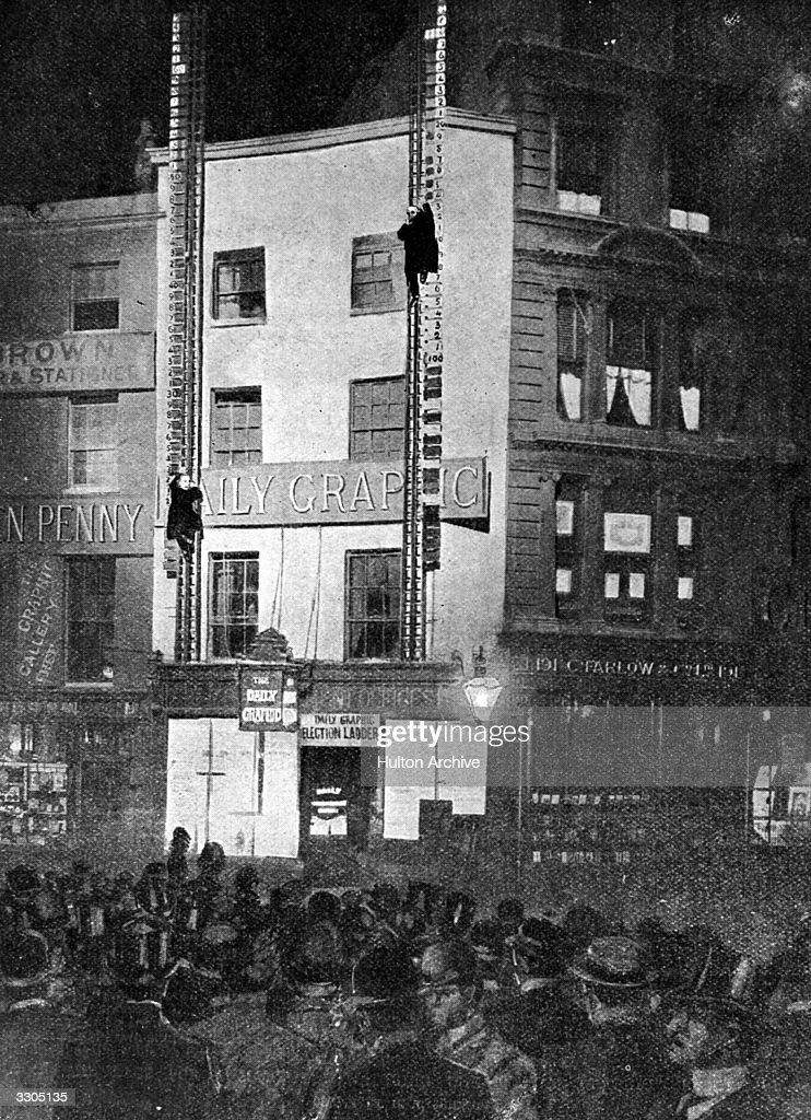 Two ladders front the Daily Graphic Office in the Strand, with life-size figures of Lord Salisbury and Sir Henry Campbell-Bannerman, climbing the ladders rung by rung in accordance with the results of seats won. A crowd is gathered to watch the results as they are announced. Original Publication: The Graphic pub. 1900