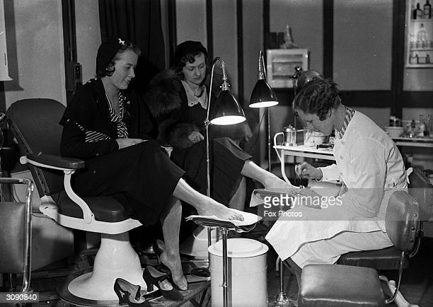 Pedicurist at the Shoe and Leather Fair in the Agricultural Hall, London paints permanent dye onto the toenails of two young ladies. The women are...