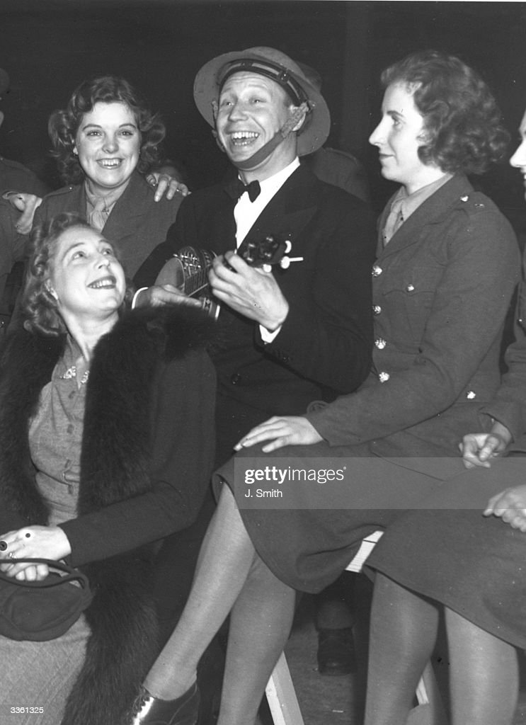 George Formby entertaining members of the ATS at a northern seaside concert hall. He and his ukelele entertained over 2000 troops, who cheered for numerous encores.