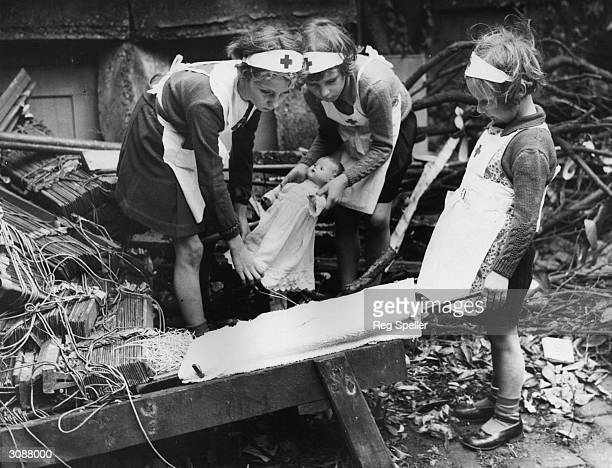 Young daughters of air raid wardens in southeast London practising first aid with the aid of their dolls in WW II