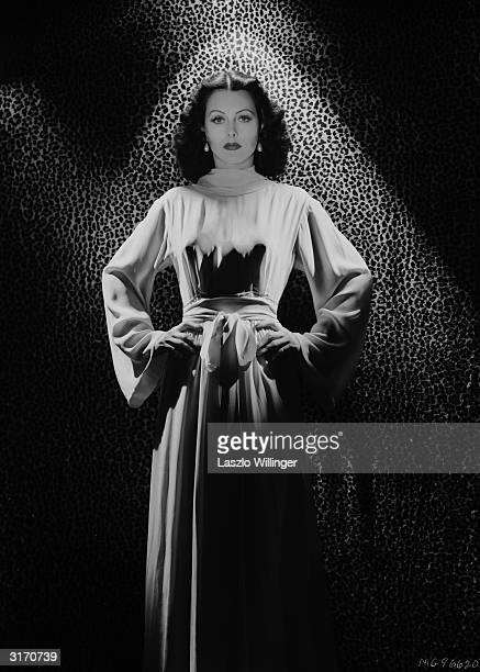 Austrian born actress Hedy Lamarr wearing a long dress in front of a leopard skin backdrop.