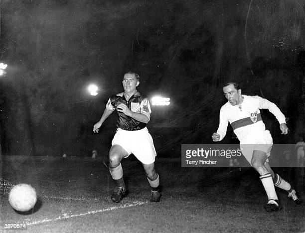 West Ham United lefthalf O'Farrell races for the ball with Baitinger the Stuttgart insideright during a floodlit match at West Ham