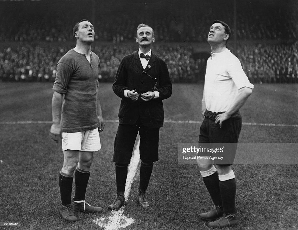 The captains of Chelsea and Tottenham Hotspur wait for the coin to drop after the referee tossed to see who kicks off.