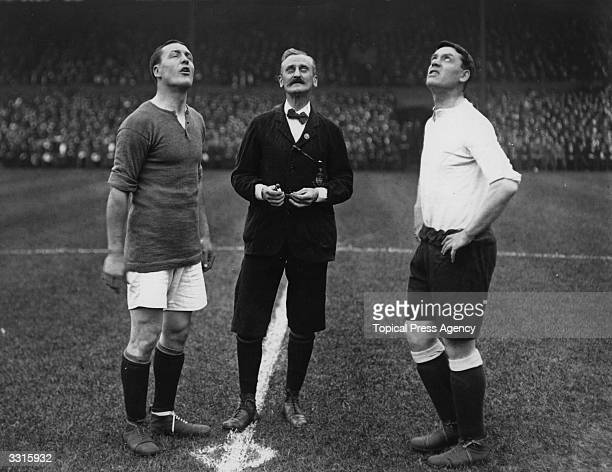 The captains of Chelsea and Tottenham Hotspur wait for the coin to drop after the referee tossed to see who kicks off