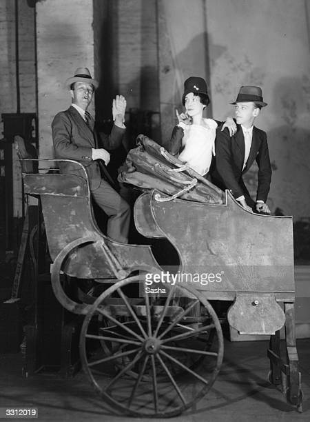Fred and Adele Astaire with Leslie Henson sitting in a coach in a scene from the play 'Funny Face'